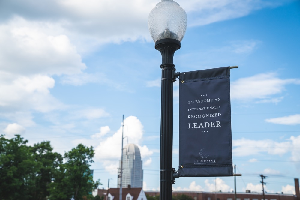 "Sign on lamp post reading ""to become an internationally recognized leader"""