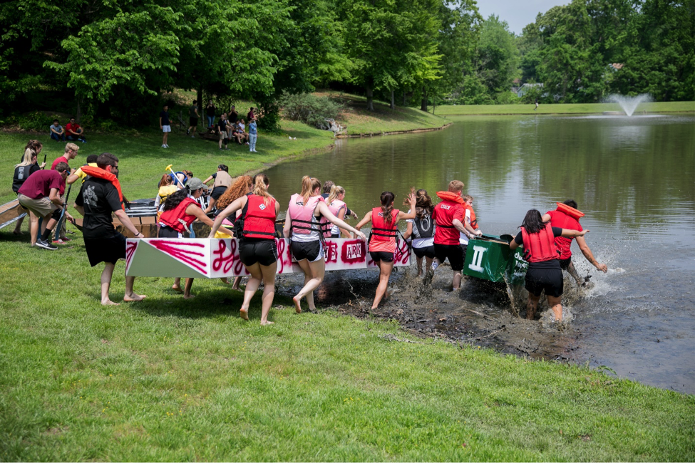 Students carrying boat into water
