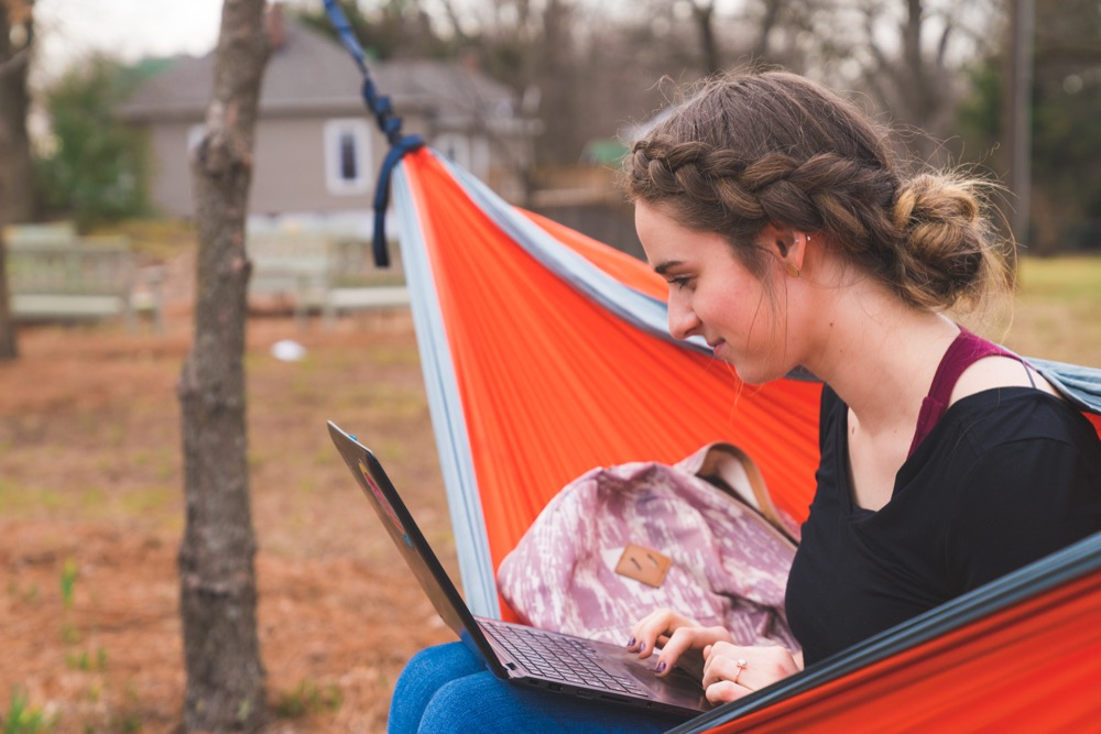 Student sitting in hammock working on laptop