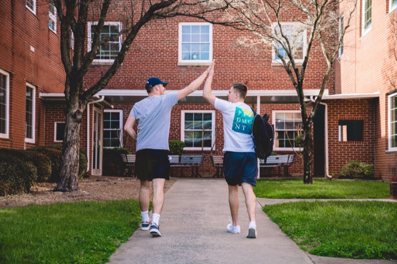 Students giving each other a high five while walking
